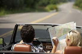 couple in convertible with map