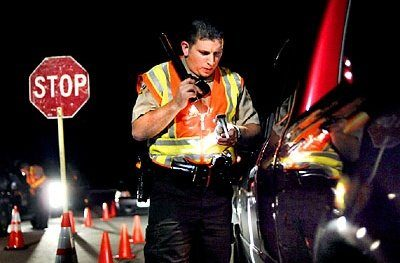 police officer checking id at DUI checkpoint